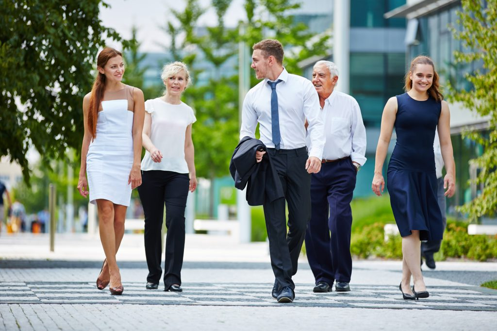 Group of business people walking and talking together outdoors in summer
